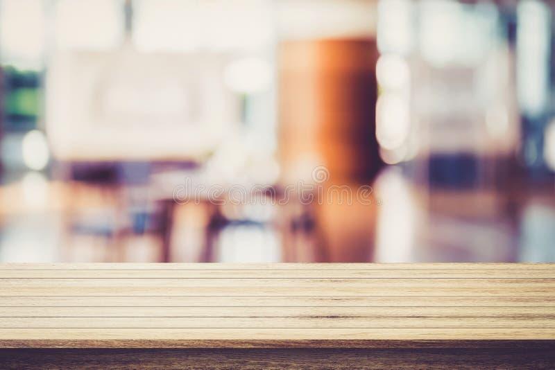 Tabla de madera vacía con el fondo de la falta de definición del restaurante fotografía de archivo