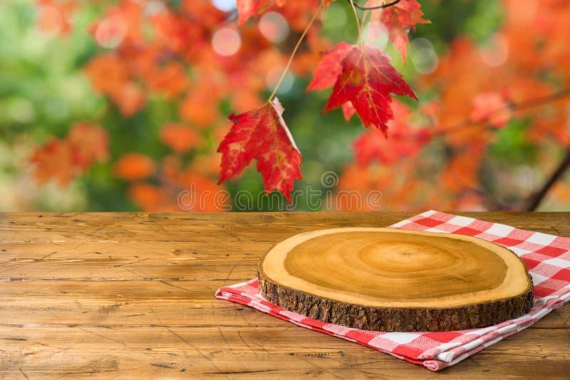Tabla de madera vacía con el mantel y tablero de madera sobre fondo del parque de naturaleza del otoño foto de archivo libre de regalías