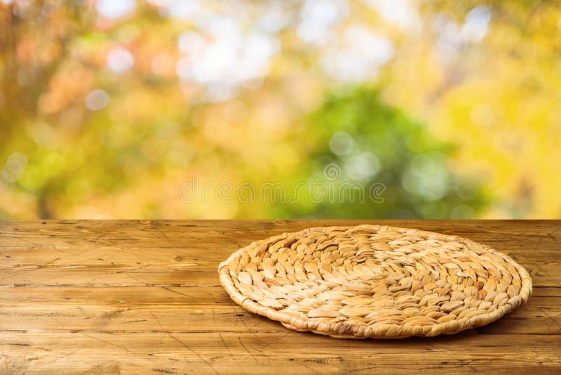 Tabla de madera vacía con el placemat redondo de mimbre sobre fondo del parque de naturaleza del otoño fotos de archivo libres de regalías