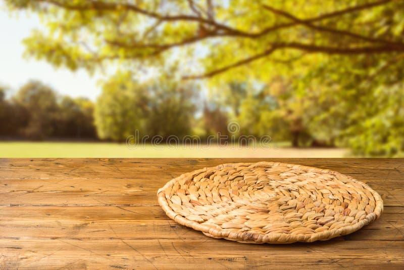 Tabla de madera vacía con el placemat redondo de mimbre sobre fondo del parque de naturaleza del otoño fotografía de archivo libre de regalías