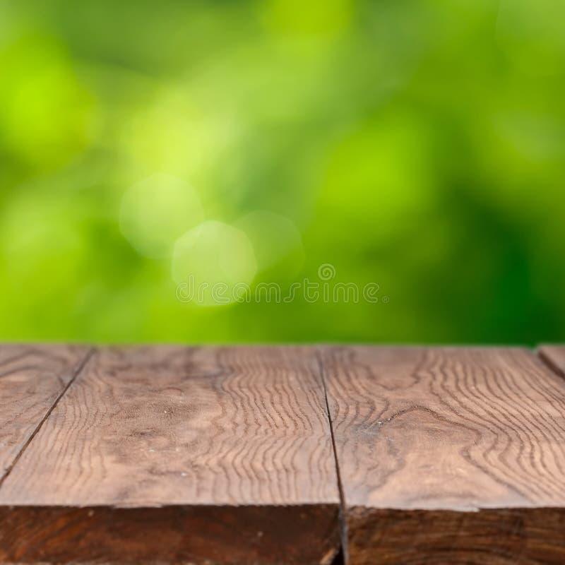 Tabla de madera vacía contra fondo verde imagenes de archivo