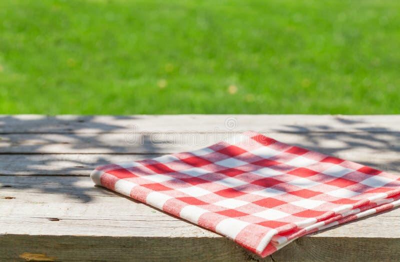 Tabla de madera vacía del jardín con el mantel foto de archivo