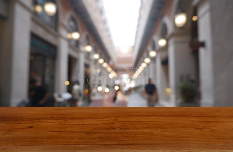 Tabla de madera vacía delante del fondo borroso abstracto del centro comercial y de la gente Puede ser utilizado para la exhibici fotografía de archivo libre de regalías