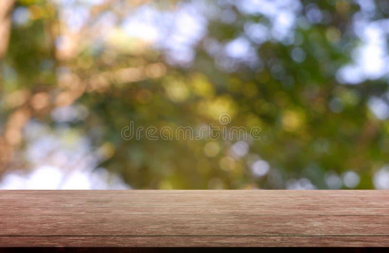 Tabla de madera vacía delante del verde borroso abstracto del fondo de la luz del jardín y de la naturaleza Para la exhibición o  imagen de archivo libre de regalías
