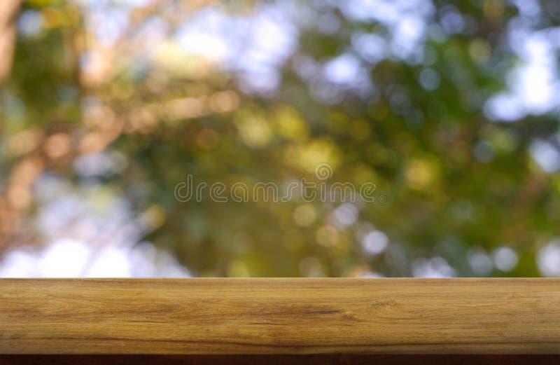 Tabla de madera vacía delante del verde borroso abstracto del fondo de la luz del jardín y de la naturaleza Para la exhibición o  fotos de archivo