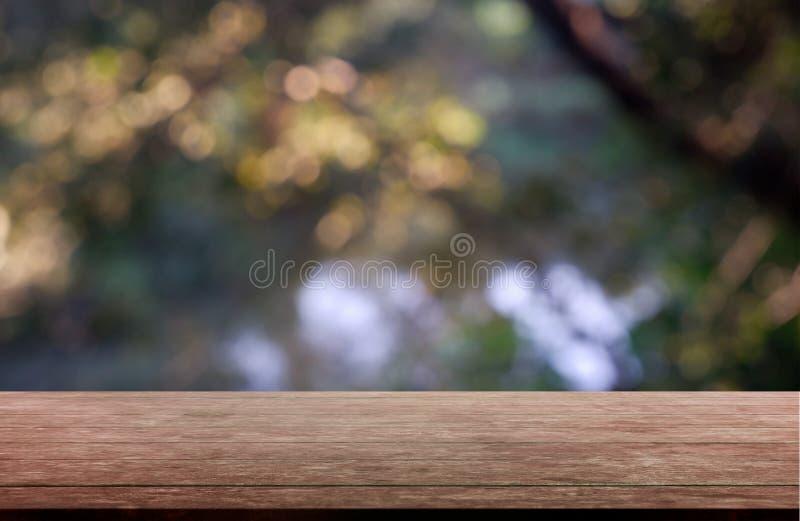 Tabla de madera vacía delante del verde borroso abstracto del jardín y de árboles Fondo r imágenes de archivo libres de regalías