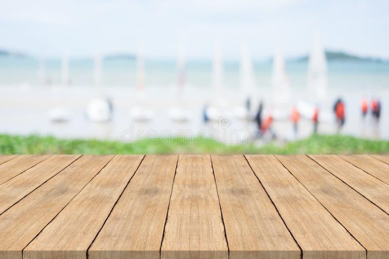 Tabla de madera vacía en frente con el fondo borroso en la playa foto de archivo