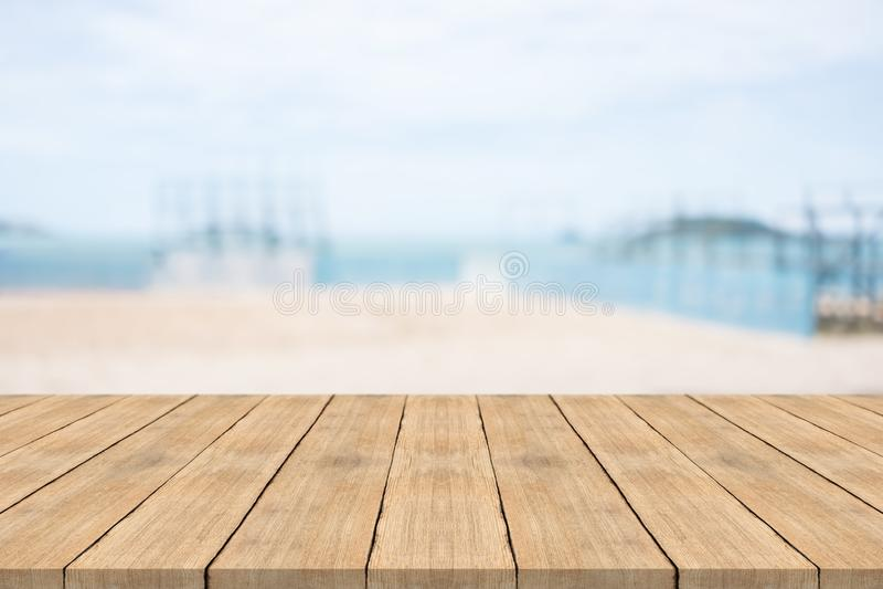 Tabla de madera vacía en frente con el fondo borroso en la playa fotografía de archivo