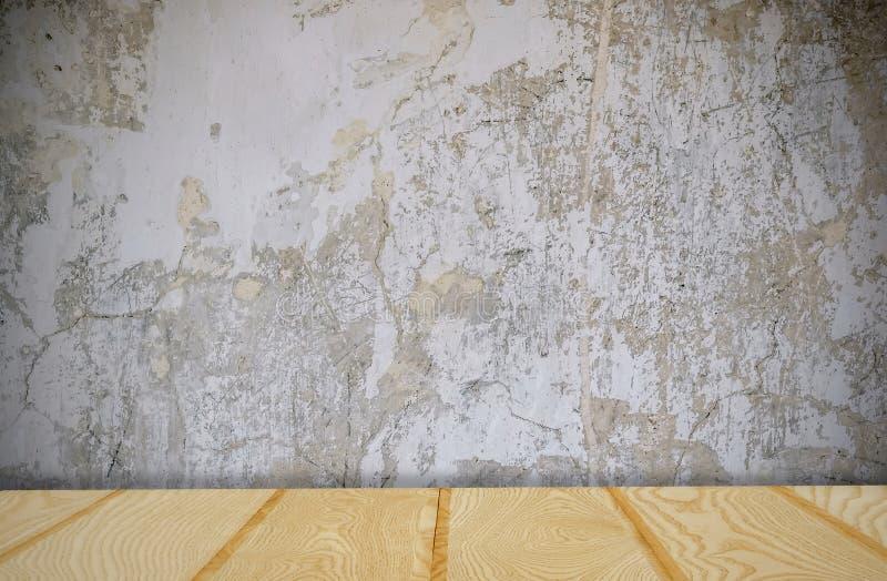 Tabla de madera vacía de la cubierta sobre la pared del cemento del grunge, fondo para el actual producto imagen de archivo