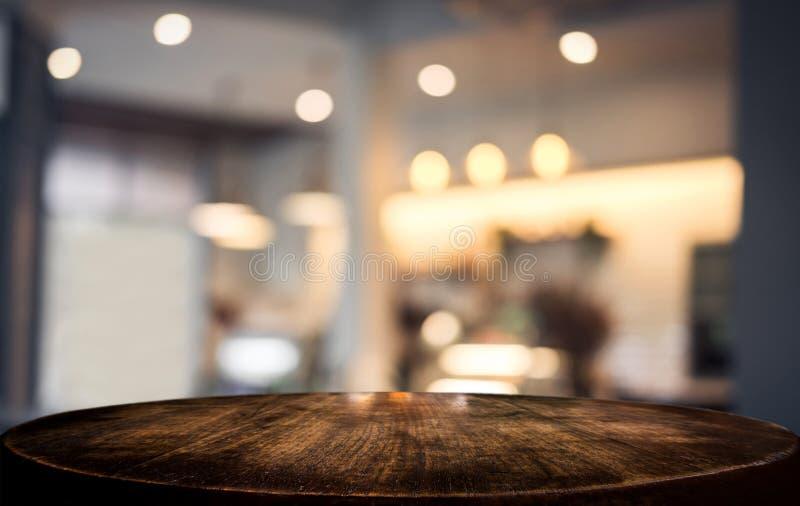 Tabla de madera vacía selectiva y fondo borroso del extracto delante de la cafetería o del restaurante para la exhibición del pro imágenes de archivo libres de regalías