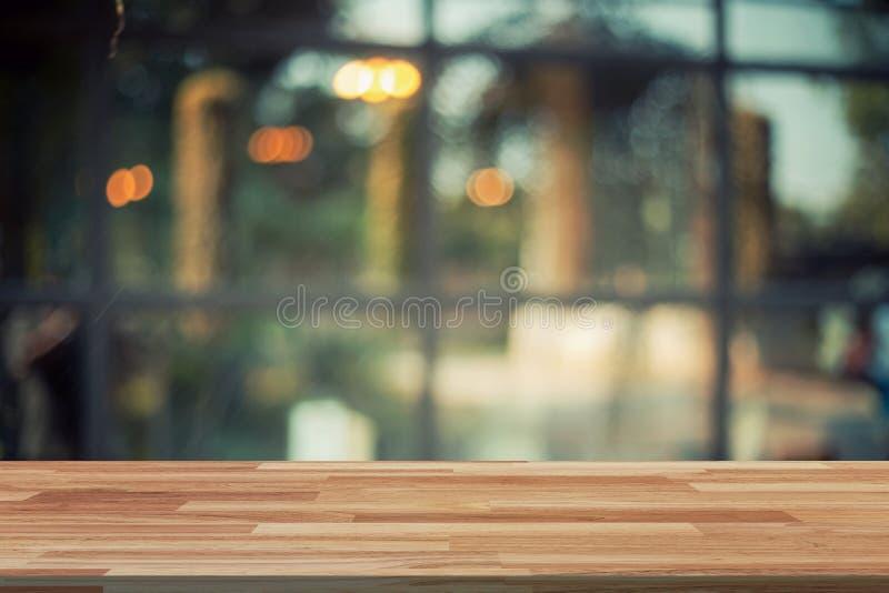 Tabla de madera vacía y exhibición borrosa del fondo en la cafetería w fotos de archivo
