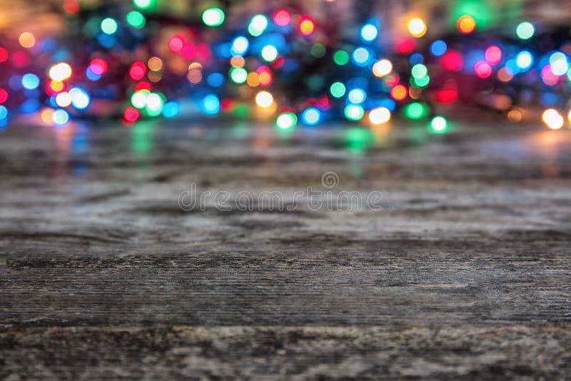Tabla de madera y fondo borroso de las luces de la Navidad fotos de archivo