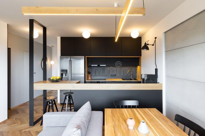 Tabla de madera y muebles elegantes de la cocina en un balneario moderno, abierto imagen de archivo libre de regalías