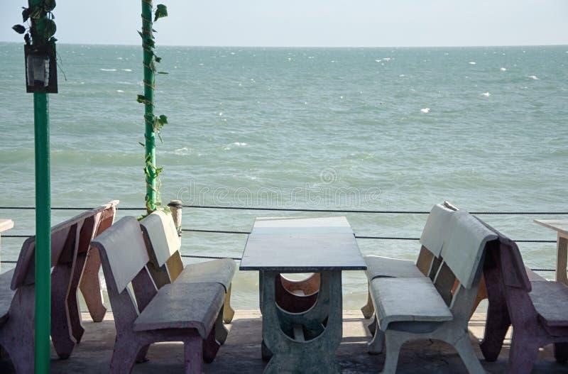 Tabla de piedra con las sillas en un café debajo de un toldo en la playa imagen de archivo libre de regalías