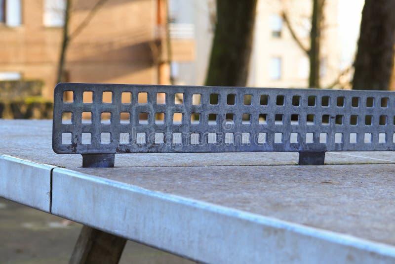 Tabla de ping-pong vieja arruinada en la yarda, con una abertura del foco en la red foto de archivo libre de regalías