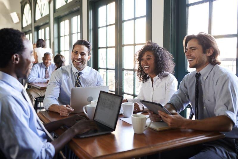 Tabla de Team Having Informal Meeting Around del negocio en cafetería imagen de archivo