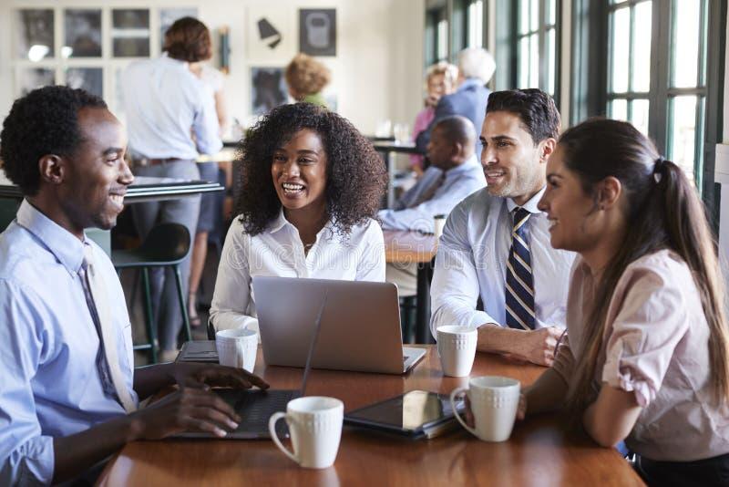 Tabla de Team Having Informal Meeting Around del negocio en cafeter?a fotos de archivo