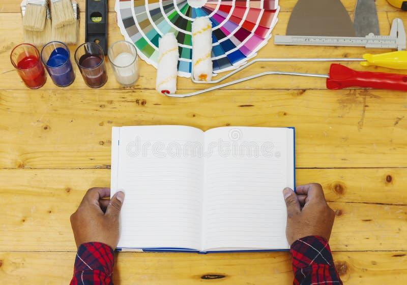 Tabla de trabajo del pintor y del decorador con proyecto de la casa, muestras del color fotografía de archivo