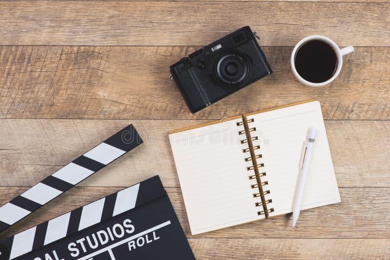 Tabla de trabajo de productor Chapaleta de la película, cámara y taza de café, encendido fotos de archivo