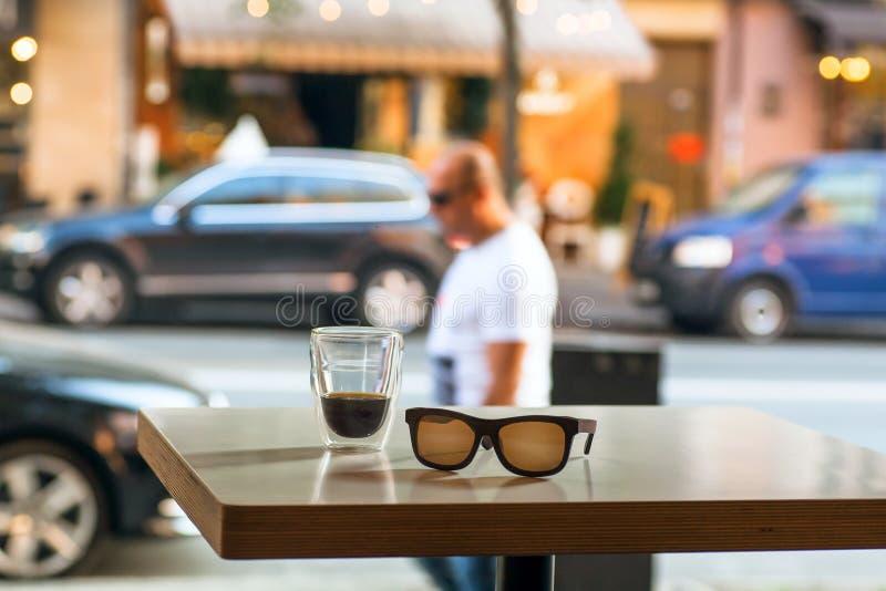 Tabla del café de la calle con el vidrio del café y el lugar vacío de un visitante que se va Concepto grande del lugar de la ciud imagen de archivo