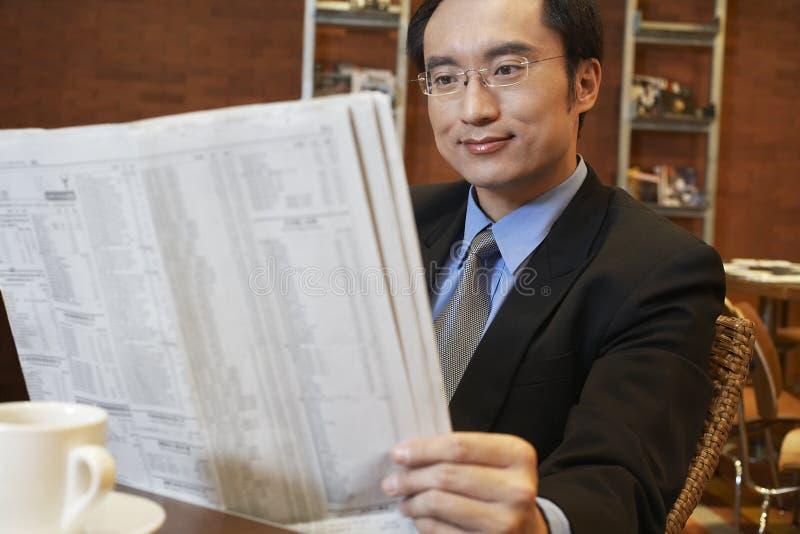 Tabla del café de Reading Newspaper At del hombre de negocios fotos de archivo libres de regalías