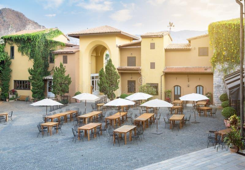 Tabla del café del restaurante con la silla y paraguas en el edificio grande foto de archivo libre de regalías