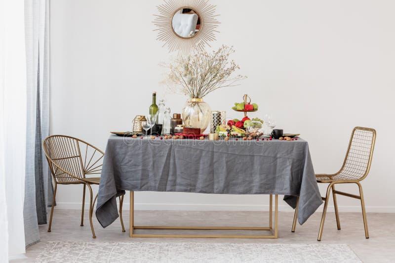 Tabla del comedor con las sillas de oro fijadas para la fiesta de cumpleaños fotografía de archivo libre de regalías