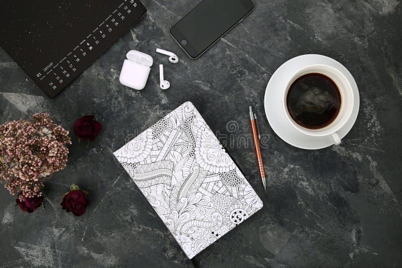 Tabla del escritorio de oficina con el cuaderno, los artilugios y las fuentes en blanco Visión superior, endecha plana imagen de archivo