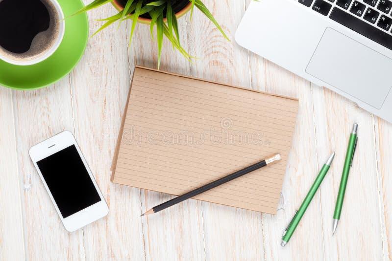 Tabla del escritorio de oficina con el ordenador, las fuentes, la taza de café y la flor fotografía de archivo libre de regalías