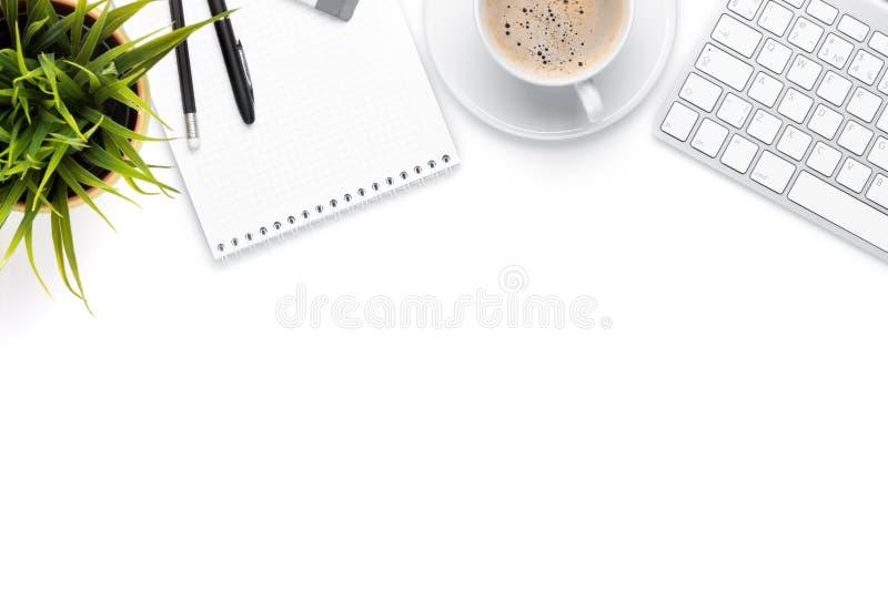Tabla del escritorio de oficina con el ordenador, las fuentes, la taza de café y la flor imágenes de archivo libres de regalías