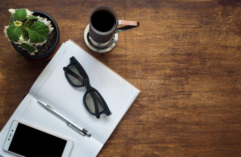 Tabla del escritorio de oficina con el teléfono de la pantalla en blanco, la pluma del cuaderno y la taza de café elegantes Visió imágenes de archivo libres de regalías