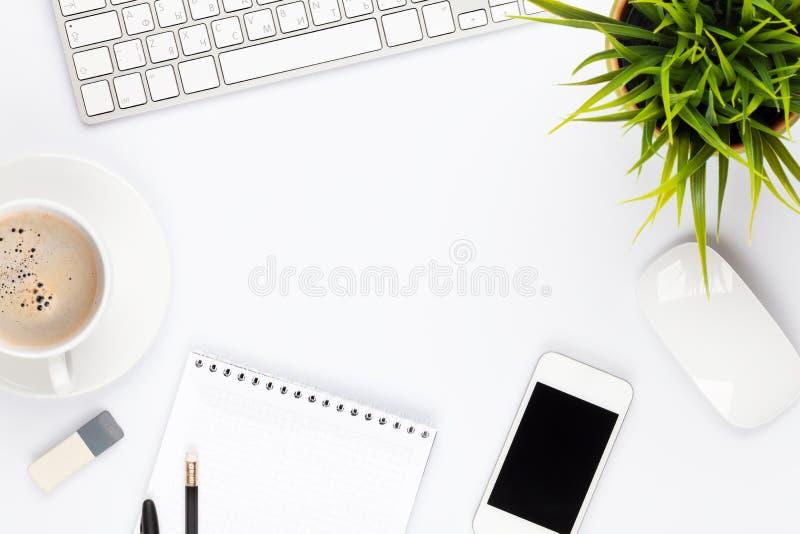 Tabla del escritorio de oficina con la taza del ordenador, de las fuentes, de la flor y de café imagen de archivo libre de regalías