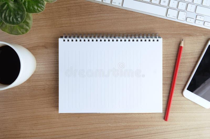 Tabla del escritorio de oficina con la taza del ordenador, del smartphone, de las fuentes, de la flor y de café imagen de archivo