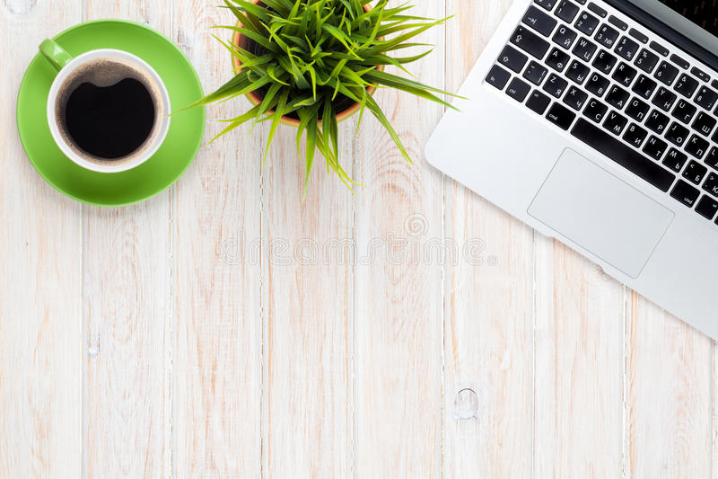 Tabla del escritorio de oficina con la taza y la flor de café del ordenador portátil foto de archivo