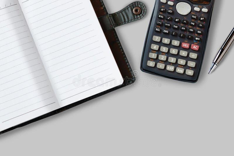 Tabla del escritorio de oficina con las fuentes, el cuaderno, la calculadora y la pluma T foto de archivo libre de regalías