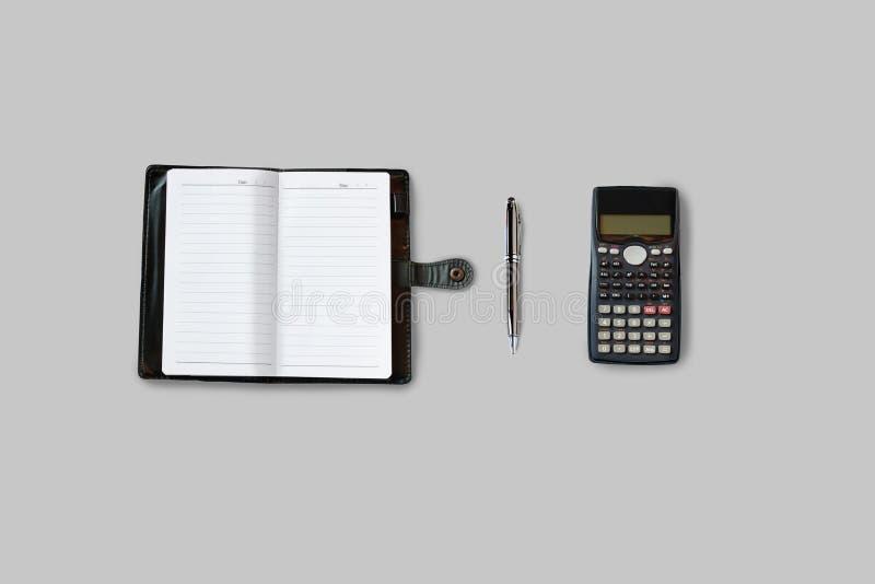 Tabla del escritorio de oficina con las fuentes, el cuaderno, la calculadora y la pluma T fotografía de archivo libre de regalías