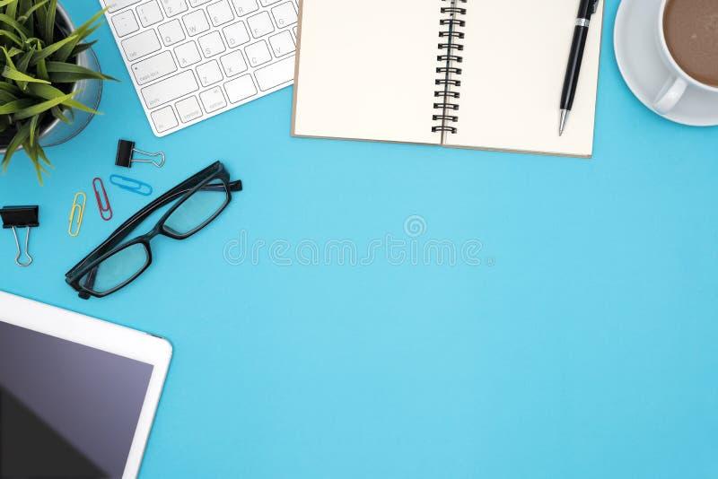 Tabla del escritorio de oficina con las fuentes y ordenador en fondo azul fotografía de archivo