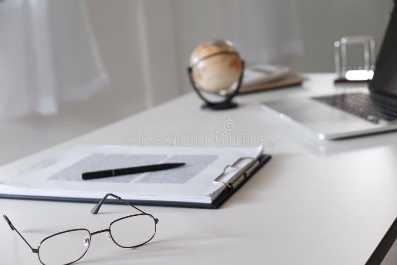 Tabla del escritorio de oficina con los vidrios, la pluma, el lápiz, el ordenador portátil y el mapa del mundo fotos de archivo libres de regalías