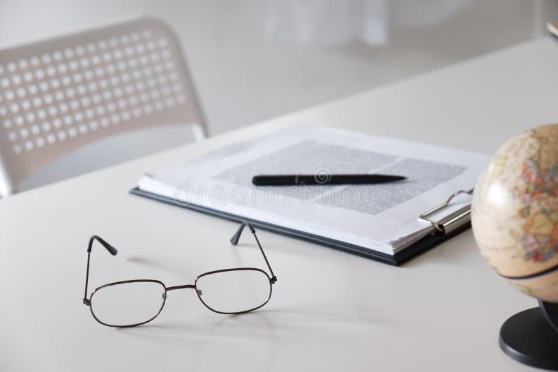 Tabla del escritorio de oficina con los vidrios, la pluma, el lápiz y el mapa del mundo imagen de archivo libre de regalías