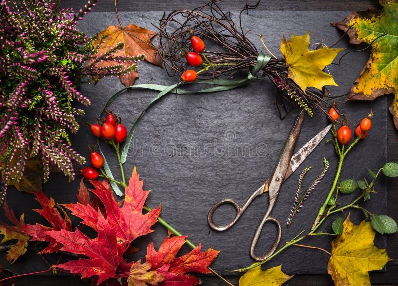 Tabla del florista para hacer decoraciones del otoño con las hojas, los esquileos y la cinta, fondo de la caída fotos de archivo libres de regalías