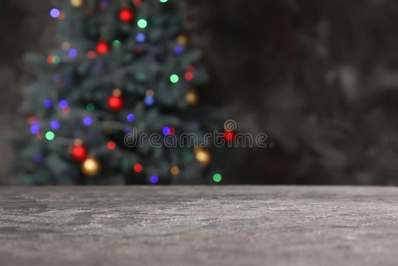 Tabla del Grunge contra el árbol de navidad que brilla intensamente imagenes de archivo