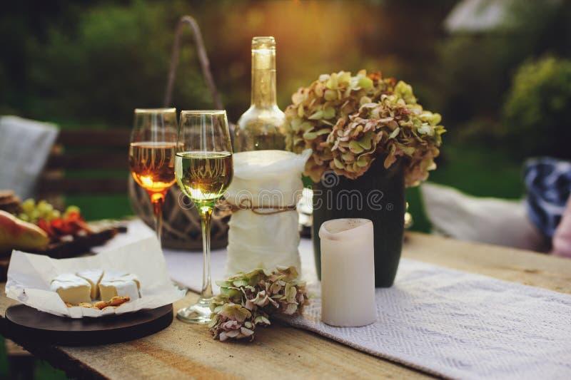 Tabla del jardín del verano adornada con las flores y las velas, partido de tarde con el vino imagen de archivo