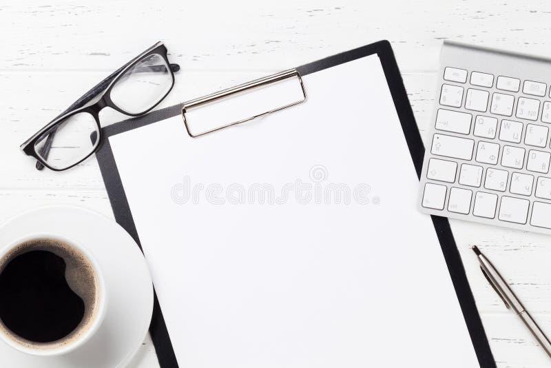Tabla del lugar de trabajo de la oficina con la p?gina de papel en blanco foto de archivo