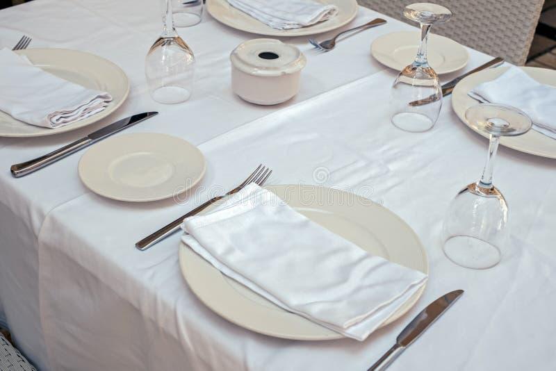 Tabla del restaurante con las servilletas vacías cubiertos y vidrios de las placas imagen de archivo libre de regalías