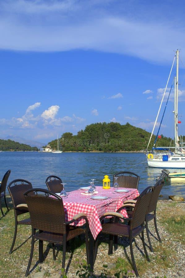 Tabla del restaurante en la costa de la bahía de Nidri, Grecia foto de archivo libre de regalías