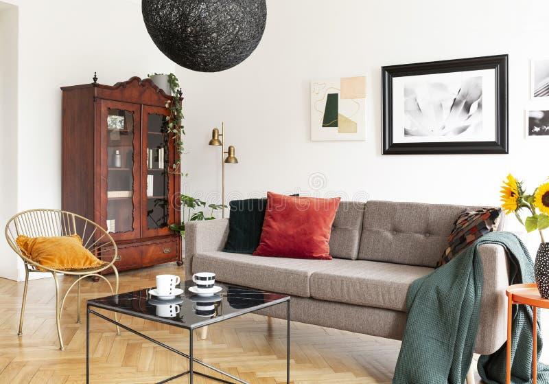 Tabla delante de la butaca y del sofá en el interio plano blanco fotografía de archivo