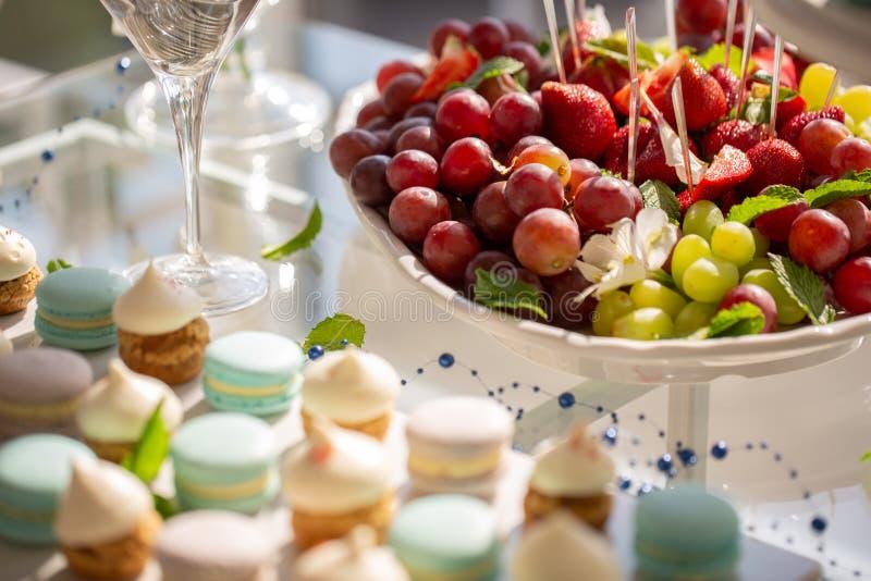 Tabla dulce de la boda con las tortas y la fresa, uvas en el top, frutas foto de archivo libre de regalías