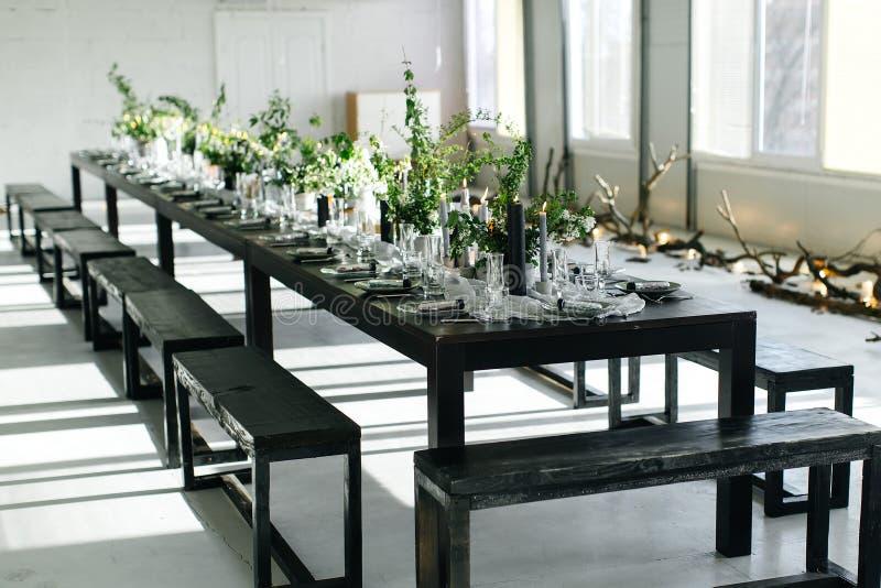 Tabla elegante, desván Sitio del diseño en el estilo del desván Tabla negra, sillas, platos, velas Tarros con verdes imagen de archivo libre de regalías