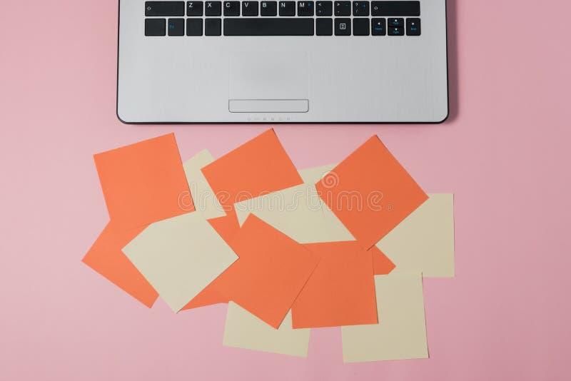 Tabla en colores pastel del escritorio de oficina con el ordenador portátil, y fuentes fotos de archivo