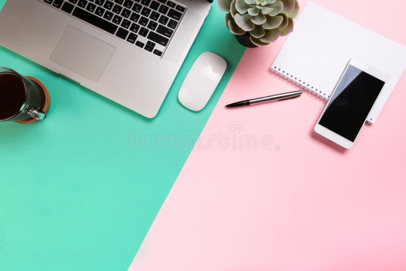 Tabla en colores pastel del escritorio de oficina con el ordenador port?til y las fuentes Visi?n superior con el espacio de la co imágenes de archivo libres de regalías